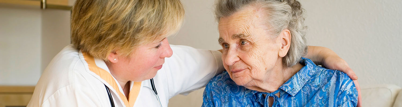 Health care professional comforting senior patient.
